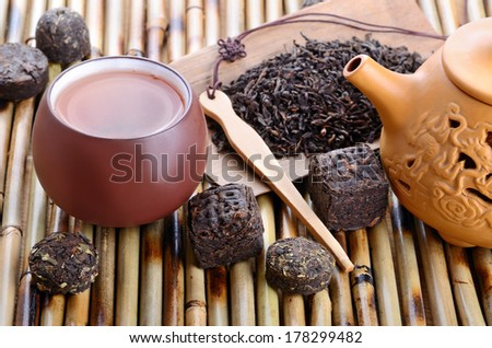 Cup of chinese pu-erh tea and dried leaves on bamboo mat background - stock photo