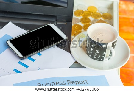 Cup of chocolate ,Printed Business Annual Report in Charts, tablet and smartphone .business concept. - stock photo