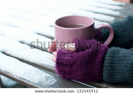 Cup of cocoa outdoors in winter and purple mittens - stock photo