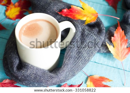 Cup of cocoa with autumn leaves abstract still life - stock photo