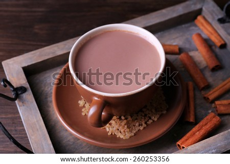 Cup of cocoa with sugar and cinnamon on wooden tray, closeup - stock photo