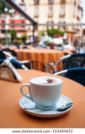cup of coffe on the table of the outdoor cafe on the italian sidewalk. Taken during Italian vacation. - stock photo