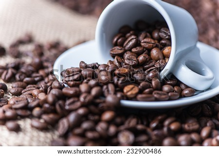 Cup of coffee. A cup of cappuccino with coffee bean as background - stock photo