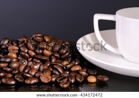 cup of coffee and beans on a glass surface - stock photo