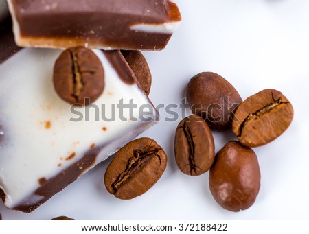 Cup of coffee and beans with delicious macaroon on a white background.