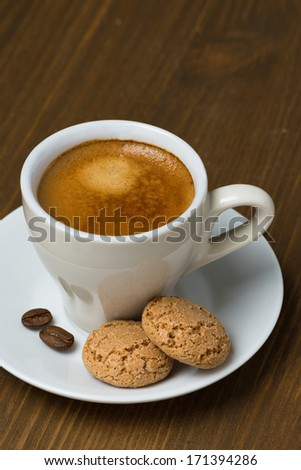 cup of coffee and biscotti on a wooden table, vertical