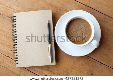 Cup of coffee and blank notebook on the wood