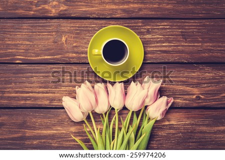 Cup of coffee and bouquet of tulips on a wooden background - stock photo