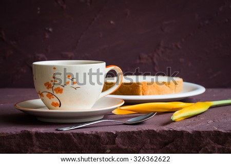 Cup of coffee and bread on stone table over grunge background, rustic style