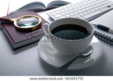 cup of coffee and business diary and loupe and keyboard