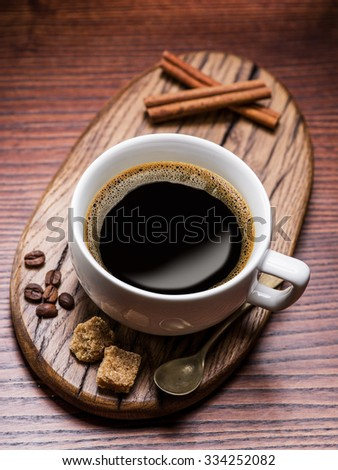 Cup of coffee and cane sugar cubes on wooden table.