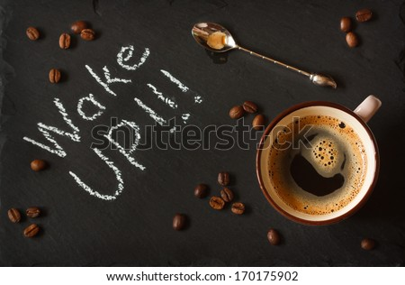 Cup of coffee and coffee beans on black chalkboard. - stock photo