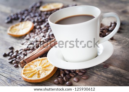 Cup of coffee and coffee beans, warm lighting. - stock photo