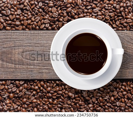 Cup of coffee and coffee beans with wooden texture background. - stock photo