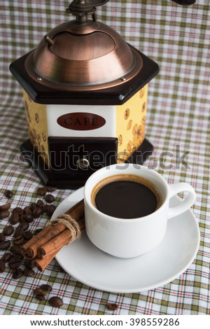 Cup of coffee and coffee mill on a light background with cinnamon and coffee beans. - stock photo