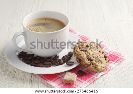 Cup of coffee and cookies with chocolate and on a light wooden table