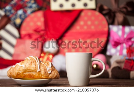 Cup of coffee and croissant on christmas background. - stock photo