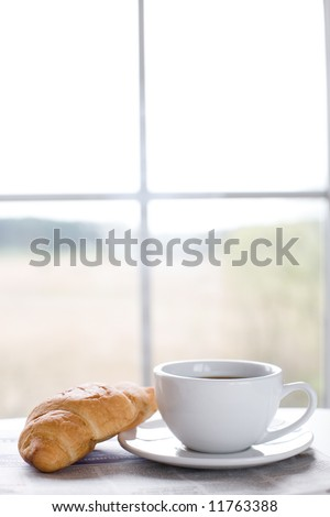 cup of coffee and croissant on the newspaper / business break - stock photo