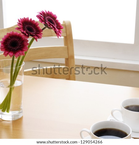 cup of coffee and daisy flowers on wooden table