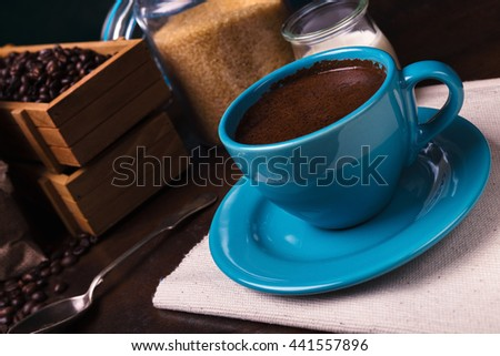 Cup of coffee and jute bags, wooden containers filled with cofee beans on the rust background. Cane sugar. Low light. - stock photo