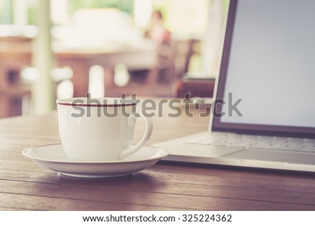 Cup of coffee and laptop computer on wooden table, warm retro style - stock photo