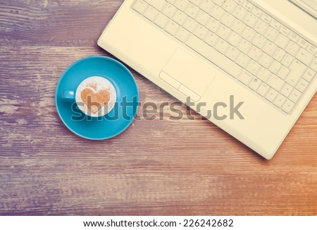 Cup of coffee and laptop on a table. - stock photo