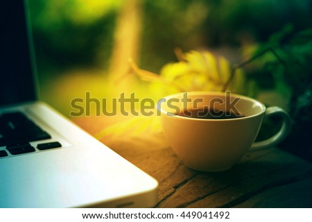 Cup of coffee and laptop on wooden table, business concept - stock photo