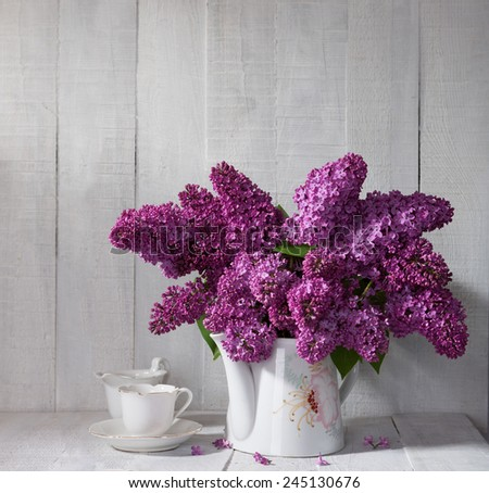 Cup of coffee and Lilac Bouquet in ceramic jug against a white wooden board. - stock photo
