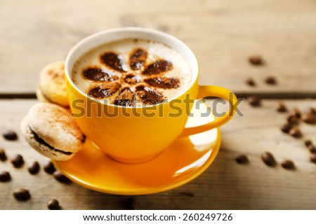 Cup of coffee  and macaroons on old wooden table - stock photo