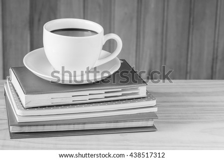 Cup of coffee and note book on wooden table background.black and white tone