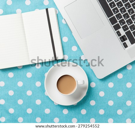Cup of coffee and notebook near laptop comuter on blue polka dot background - stock photo