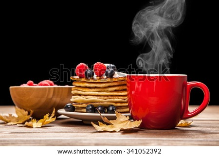 Cup of coffee and pancakes with berries - stock photo