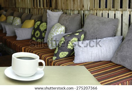 cup of coffee and pillow on sofa at restaurant blur background - stock photo