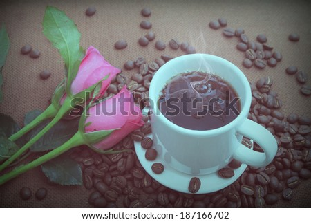 Cup of coffee and pink rose with vintage filter effect - stock photo