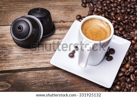 Cup of coffee and pods on wooden table - stock photo