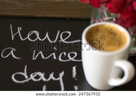 Cup of coffee and red cloves flowers in a vase with good morning note - stock photo