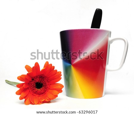 Cup of coffee and red flower on white background