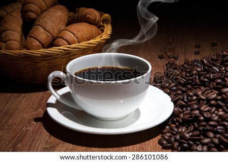 cup of coffee and roasted beans with croissants