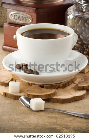 cup of coffee and roasted beans with grinder - stock photo