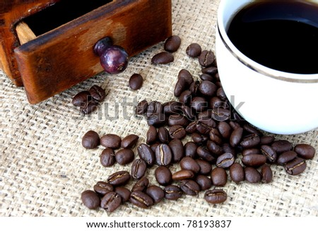 cup of coffee and spilled beans - stock photo