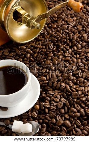 cup of coffee and spoon on roasted beans as background - stock photo