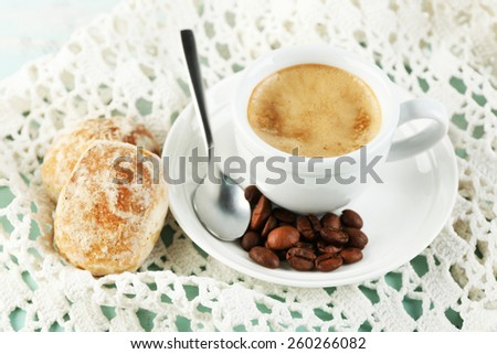 Cup of coffee and tasty cookie on color wooden background - stock photo