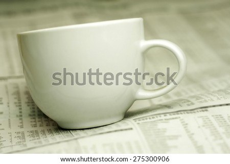 cup of coffee and the newspaper with a very shallow depth of field with copy space for text - stock photo