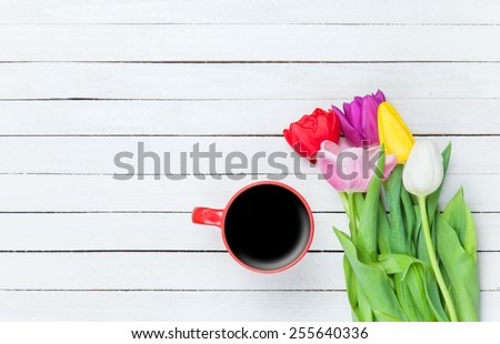 Cup of coffee and tulips on a white wooden background. - stock photo