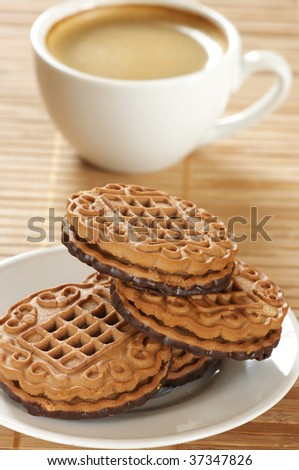 Cup of coffee and two cookies on wooden mat.