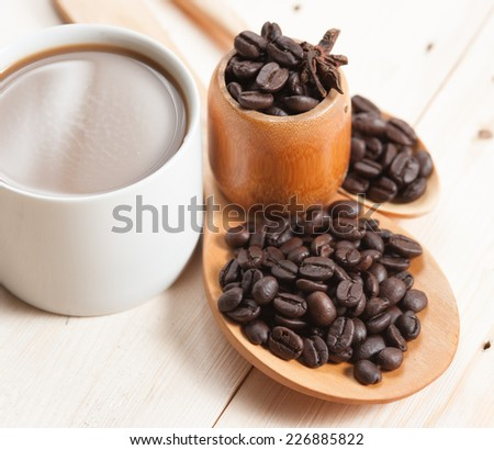 cup of coffee and Wooden Spoon on wood table, selective focus - stock photo
