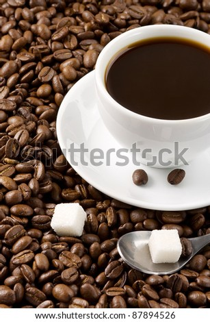 cup of coffee at roasted beans as background - stock photo