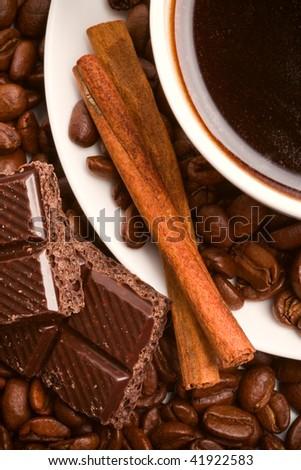 cup of coffee, beans, cinnamon sticks and black chocolate closeup - stock photo