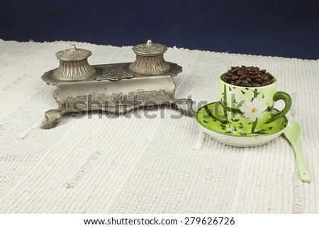 cup of coffee beans on the table with Art Nouveau inkwell, background for text - stock photo
