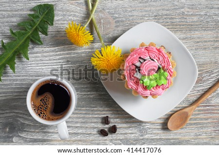 Cup of coffee, cake and flowers on old wooden table, top view - stock photo